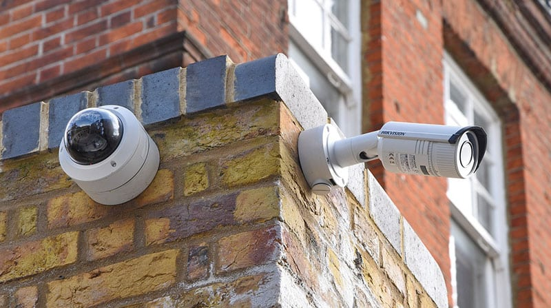 CCTV cameras mounted on the exterior brick walls of a commercial property